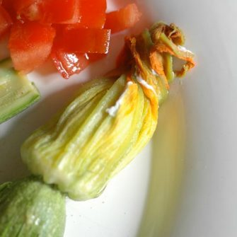 Courgette flowers stuffed with Robiola Osella on a layer of tomatoes